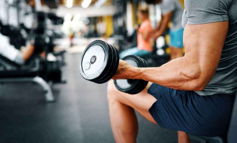 fit guy doing bicept curls in gym